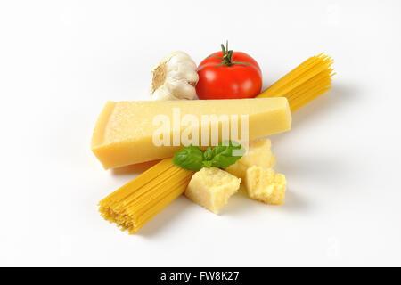 Fromage parmesan frais, garniture de légumes et l'ensemble de matières les spaghettis sur fond blanc Banque D'Images