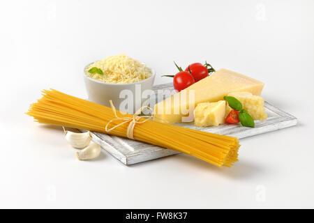 Fromage parmesan frais, garniture de légumes et l'ensemble de matières sur spaghetti planche à découper en bois Banque D'Images
