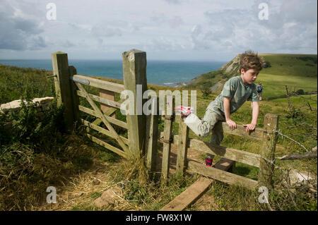Un jeune garçon est en retard sur sa famille comme ils vont sur une promenade le long du chemin de la falaise dans Banque D'Images