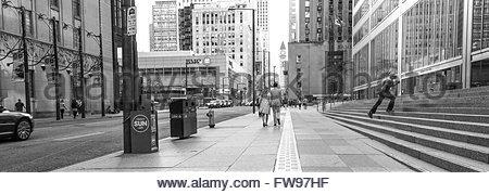 Dans l'amour et sur l'Aller - Couple marchant sur le trottoir au centre-ville de Toronto. Les courses de jeune homme Banque D'Images