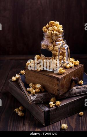 Certains du maïs soufflé sucré en verre placé sur une pile de livres Banque D'Images