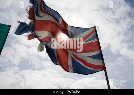 Un vieux et un peu usés union jack flag de la Grande-Bretagne ou le Royaume-Uni volant dans la brise. Banque D'Images