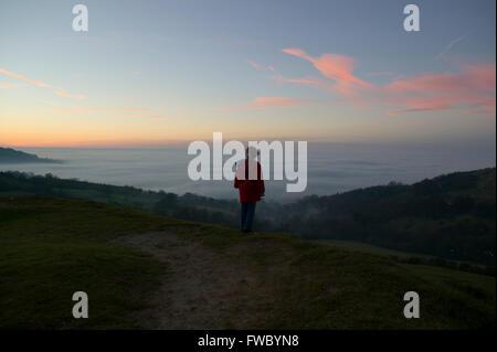 Une jeune fille debout sur une colline regardant le coucher du soleil et la brume rassemble dans la vallée ci-dessous. Banque D'Images