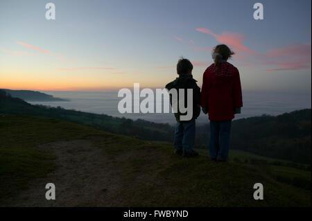 Deux jeunes enfants debout sur une colline regardant le coucher du soleil alors que la nuit tombe et la brume rassemble Banque D'Images