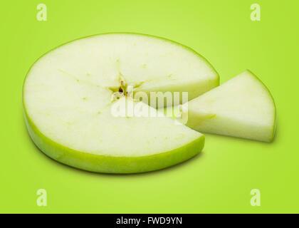 Tranches de pomme verte isolée sur fond vert comme l'un des graphiques à secteurs dans toute la profondeur de champ. Banque D'Images