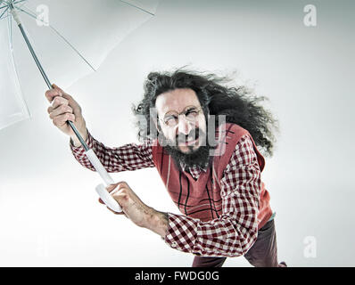 Funny portrait of a young nerdy guy holding an umbrella Banque D'Images