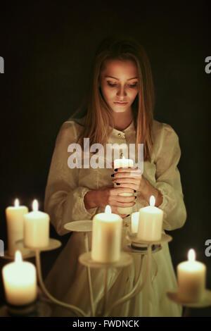 Jeune femme avec une bougie dans la main . Concept surréaliste et gothique Banque D'Images