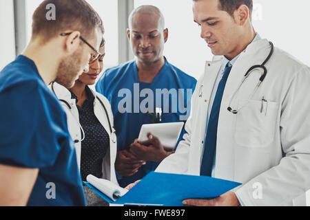 Les médecins ayant une conversation à la recherche de documents, de races mixtes, les chirurgiens et médecins Banque D'Images