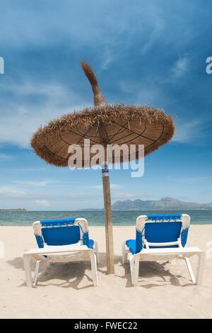 Plage Parasols et chaises longues sur la plage de Pollensa, Pollensa, Mallorca, Baleares, Espagne Banque D'Images