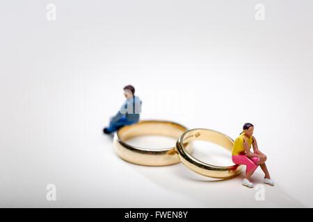 Concept de droit d'un couple assis sur les anneaux de mariage pour illustrer le divorce et la séparation Banque D'Images