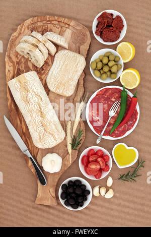 Sélection d'antipasti italiens avec des olives, salami, des piments séchés au soleil, et légumes frais huile d'olive et pain ciabatta