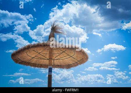 Une paille Beach Parasol, parasol, contre un ciel nuageux bleu sur une journée d'été sur la plage de Pollensa, Pollensa, Banque D'Images