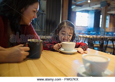 Mère fille regardant lécher du chocolat chaud dans un café Banque D'Images