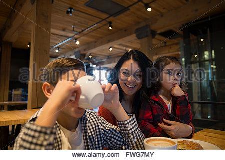 Smiling mother watching fils de boire du café dans une boulangerie Banque D'Images