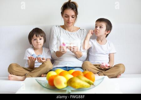 Jeune mère de deux garçons, holding test de grossesse positif, deux enfants, chacun de son côté tenue rose et bleu Banque D'Images
