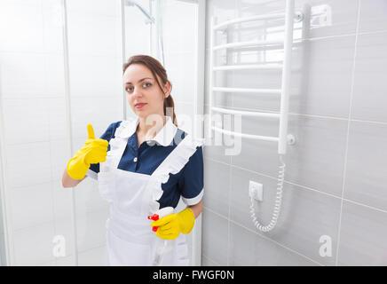 Certains jeunes employée de maison standing in robe bleue et tablier blanc avec Thumbs up geste tout en maintenant à côté de cabine de douche dans la salle de bains.