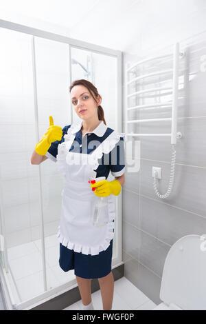 Seul confident female domestic worker standing in robe bleue et tablier blanc avec Thumbs up tout en maintenant des gestes vaporisateur dans la salle de bains.