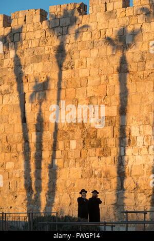 Deux Jewsh orthodoxe avec palm tree shadows en arrière-plan le long des murs de la vieille ville, Vieille Ville Banque D'Images