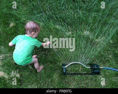 Portrait de l'enfant jouant par sprinkleurs On Grassy Field