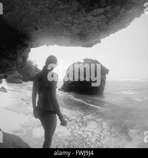 Vue arrière du Woman Standing Under Rock Formation At Beach Banque D'Images