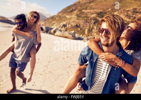 Usurpation de jeunes hommes femmes au bord de la mer. Mixed Race jeunes appréciant les vacances d'été à la plage. Banque D'Images