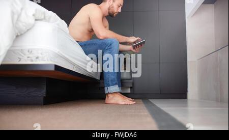 Portrait de côté un jeune homme assis sur le lit dans la chambre et à l'aide de tablette numérique. Banque D'Images