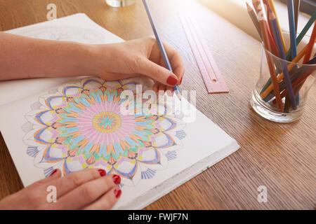 Image Gros plan femme de mains en dessin à colorier d'adultes sur une table à la maison. Banque D'Images