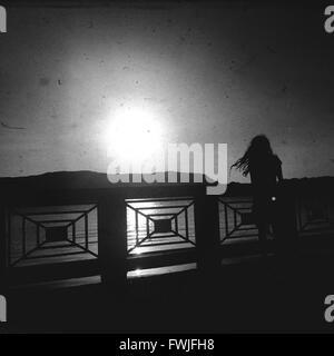 Silhouette debout sur la passerelle sur la rivière contre le Ciel clair Banque D'Images