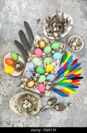 Composition de Pâques avec des oeufs colorés et des plumes d'oiseaux. Vue d'en haut. Photo couleur style vintage Banque D'Images