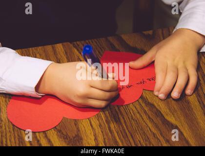 Portrait de l'enfant écrit sur carte de Vœux en forme de coeur sur table Banque D'Images
