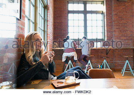 Smiling young woman drinking tea in coffee shop Banque D'Images