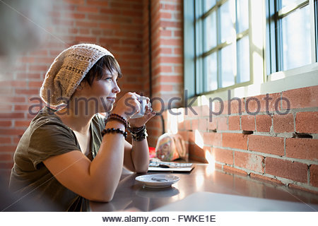 Pensive young woman drinking coffee in coffee shop Banque D'Images