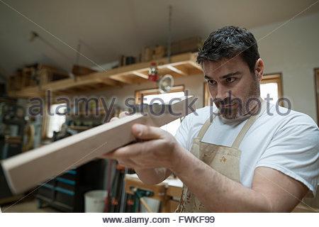 Carpenter l'examen de la cale en bois en atelier Banque D'Images