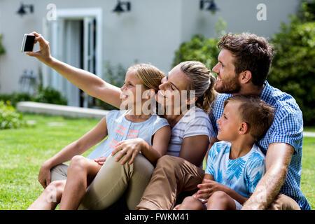 Heureuse fête en tenant dans la cour avec la famille selfies Banque D'Images