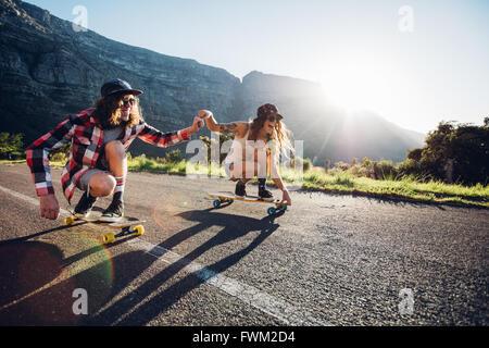 Happy young couple having fun with skateboard sur la route. Jeune homme et femme patiner ensemble lors d'une journée Banque D'Images