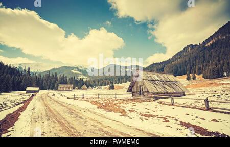 Huttes de bois aux tons Vintage par une route dans les montagnes de Tatra, fin de l'hiver et début de printemps, Banque D'Images
