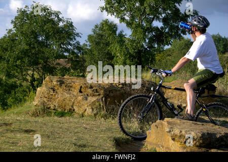 Cycliste sur Ham Hill, Somerset, Angleterre, les gens jeune homme reposant repose sur l'eau de boisson potable rock bouteille vélo assis