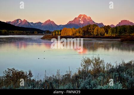 WYOMING - Lever du Soleil vu depuis les rives de la rivière Snake à partir de Oxbow Bend avec Mont Moran s'élevant Banque D'Images