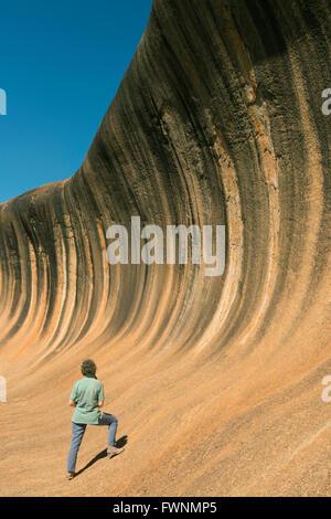Femme et Wave Rock, suppression de la formation de granit, l'ouest de l'Australie Banque D'Images