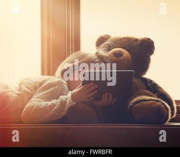 Une petite fille est maintenant une technologie comprimé dans une fenêtre ensoleillée à la maison avec un ours en peluche pour un concept de loisirs divertissement