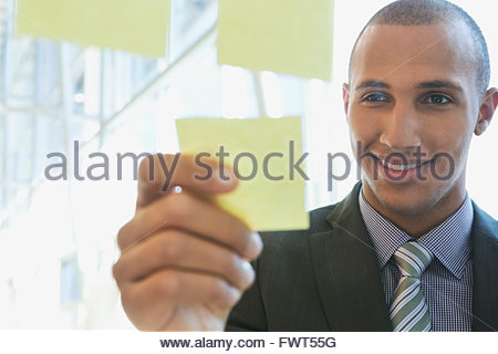 Young businessman putting sticky note sur verre Banque D'Images