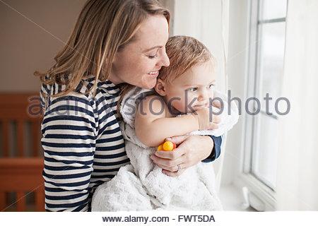 Mère se pelotonnant baby girl après son bain Banque D'Images