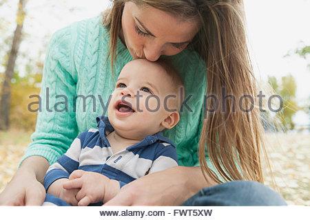 Mère embrassant fils tête à park Banque D'Images