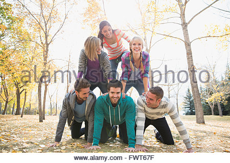 Les amis formant une pyramide humaine in park Banque D'Images