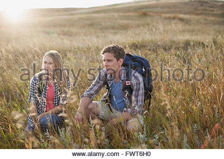 Couple accroupi dans les champs. Banque D'Images