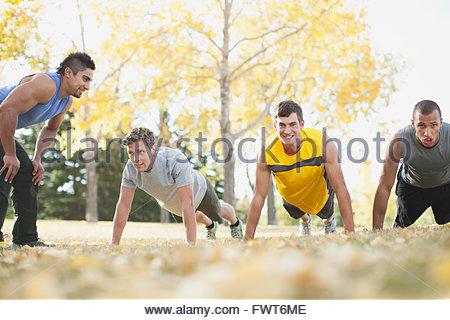 Formateur en encourageant les hommes dans la catégorie remise en forme en plein air. Banque D'Images
