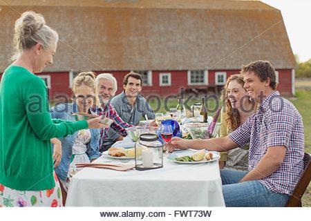 Femme montrant des pie pour famille à repas en plein air. Banque D'Images