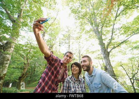 Multi-ethnic group of friends en tenant à un camp site selfies Banque D'Images