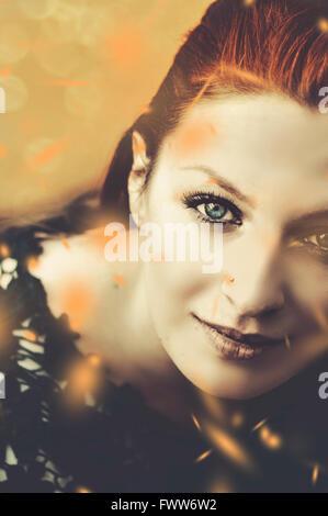 Portrait de la belle femme avec les feuilles qui tombent