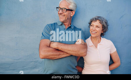 Portrait of a young couple et à l'écart et souriant contre fond bleu. L'homme et de la femme d'âge moyen le Banque D'Images